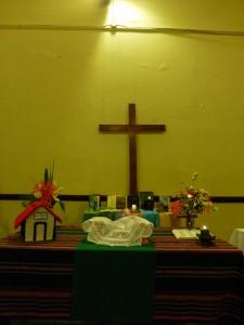 la mesa de comunión: flores, la casita, pan y vino. Atrás las Biblias de hermanos y hermans de la iglesia en homenaje por el día de la Biblia